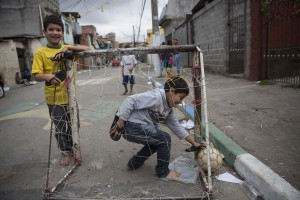 SAO PAULO, BRAZIL - JUNE 21: Children play football in the street in the poor neighbourhood of Itaquera, adjacent to the 'Arena de Sao Paulo' stadium, on June 21, 2014 in Sao Paulo, Brazil. The Arena de Sao Paulo, which is reported to have cost in excess of 200 million GBP, hosted the opening match of the 2014 FIFA World Cup and has a capacity of over 61,000. The total cost borne by Brazil for staging the 2014 World Cup is estimated to be 6.5 billion GBP, which critics have argued would have better spent on the millions of Brazilians living in poverty. (Photo by Oli Scarff/Getty Images) ORG XMIT: 498990827